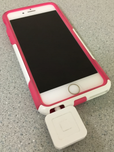 Photo of Square reader attached to iPhone